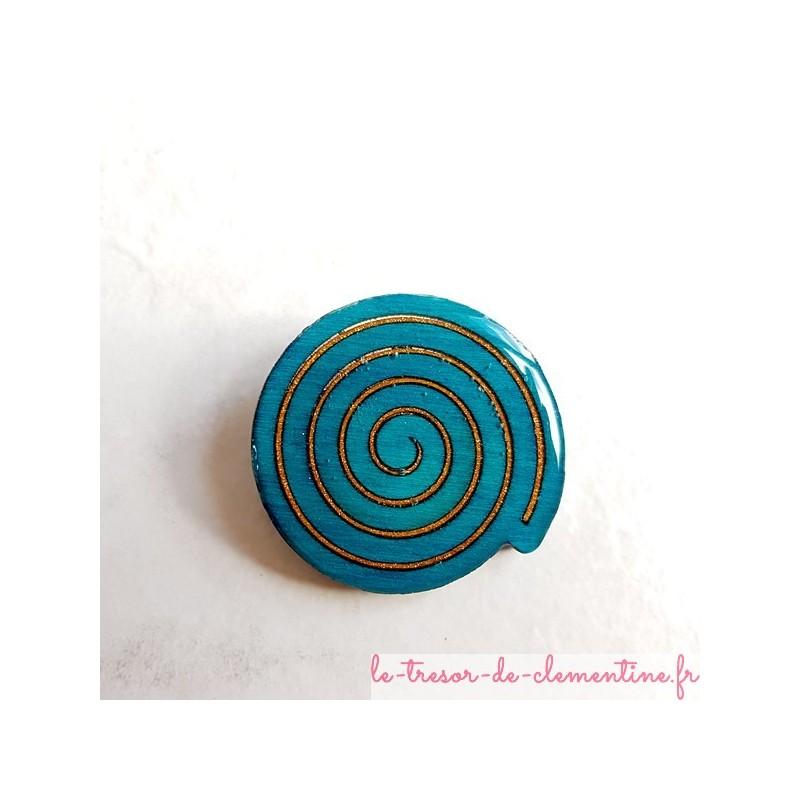 Broche artisanale en forme spirale turquoise et bronze scintillant avec léger ajourement entre les spirales encastrées.