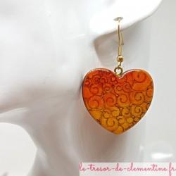 Boucle d'oreille fantaisie coeur à volutes orange ton feu pour femme monture dorée