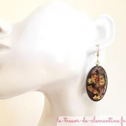 Jolie paire de boucles d'oreilles pendantes femme noir et or pailleté, elle forme ovale, aspect émail.